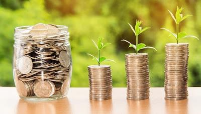 vidro com moedas e três pilhas de moedas com mudas de planta em cima