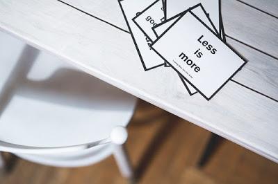 frase-menos-e-mais-em-cartao-em-cima-de-uma-mesa