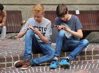 dois-garotos-olhando-mensagens-nos-seus-celulares