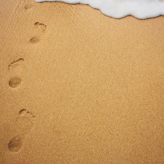 pegadas-na-areia-da-praia