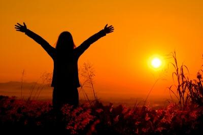 mulher-de-bracos-abertos-ao-por-do-sol