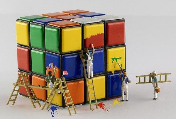 cubo de rubik sendo pintado por homens em miniatura