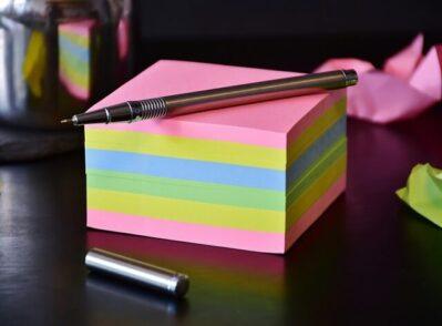 bloco de notas com folhas coloridas e caneta
