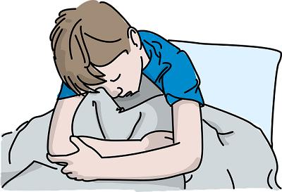 Garoto triste na cama, cabisbaixo e abraçando o cobertor