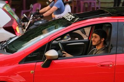 homem sorrindo em seu carro de luxo