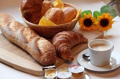 pão, geleias, café com leite e flores em mesa